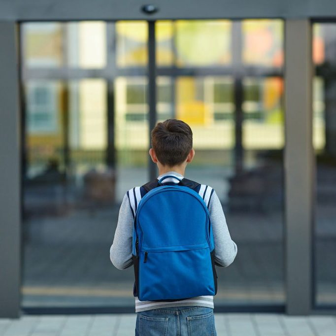 young male student stands in front of school wearing a backpack, facing away from the camera.