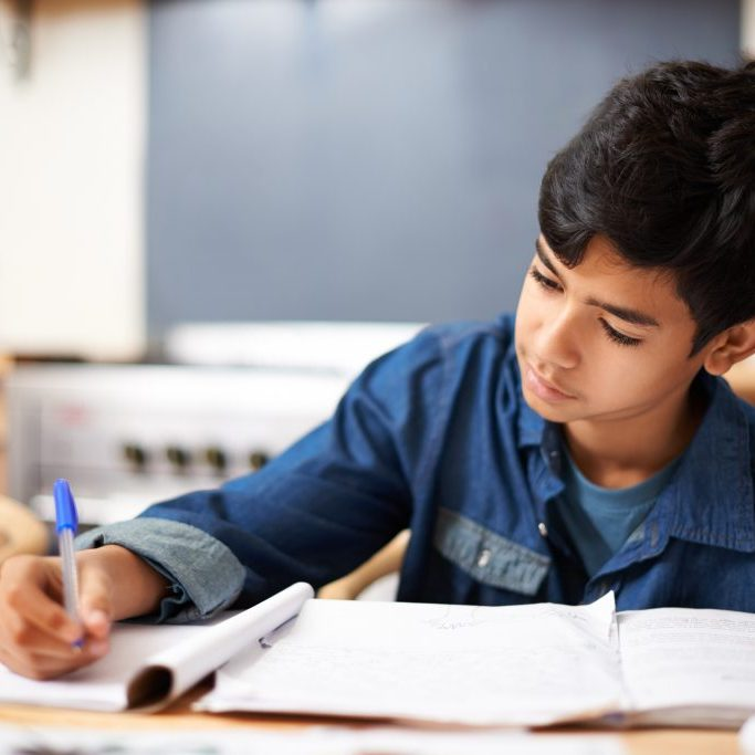 Young male student of color writes in a workbook at school.
