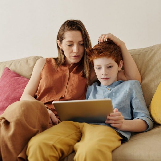 Mother and son work on a tablet computer.